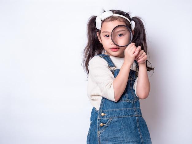 Aziaat weinig leuk meisje die een vergrootglas en het kijken houden. een klein meisje dat vergrootglas bekijkt Premium Foto