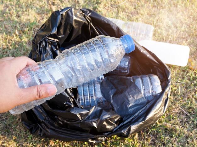 Aziaten verzamelen afval met plastic flessen water in zwarte vuilniszak. vrijwilligers beschermen het milieu door het park en de natuur schoon te maken. Premium Foto