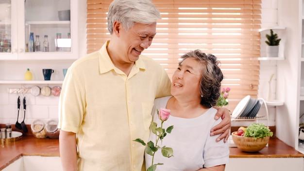 Aziatisch bejaard paar die het gelukkige glimlachen houden en bloem houden en aan camera kijken terwijl in keuken thuis ontspan. levensstijl senior familie geniet van tijd thuis concept. portret dat camera bekijkt. Gratis Foto