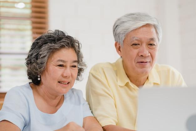 Aziatisch bejaard paar die laptop conferentie met arts over geneeskundeinformatie gebruiken in woonkamer Gratis Foto