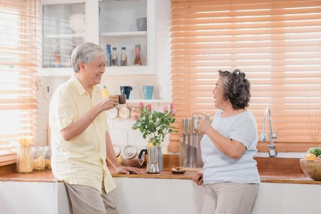 Aziatisch bejaard paar die warme koffie drinken en samen in keuken thuis spreken. Gratis Foto