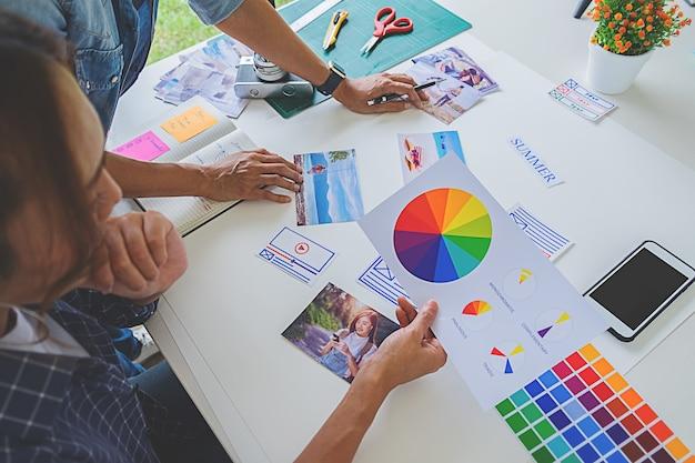 Aziatisch creatief de startteam dat van de reclameontwerper ideeën in bureau bespreekt. Premium Foto