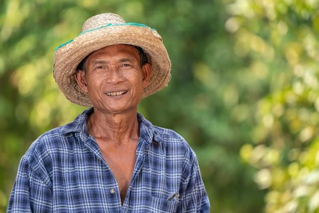 Aziatisch de plaidoverhemd van de landbouwersslijtage gelukkig in de tuin Premium Foto