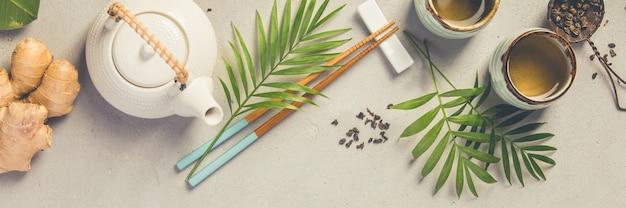 Aziatisch eten concept - thee en eetstokjes op een grijze betonnen achtergrond Premium Foto