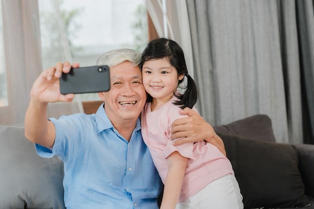 Aziatisch grootvader en kleindochter videogesprek thuis. hogere chinese opa gelukkig met jong meisje die mobiel telefoonvideogesprek met behulp van die met haar papa en mamma spreken die in woonkamer thuis liggen. Gratis Foto
