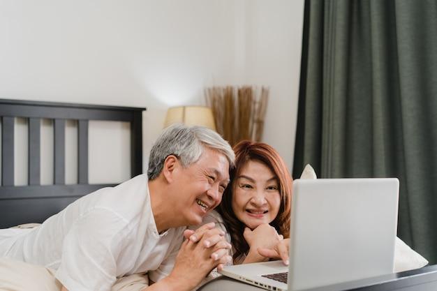 Aziatisch hoger paar dat laptop thuis met behulp van. aziatische hogere chinese grootouders, echtgenoot en vrouw gelukkig na kielzog omhoog, lettend op film liggend op bed in slaapkamer thuis in het ochtendconcept. Gratis Foto