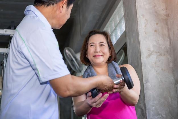 Aziatisch hoger paar die in sportkleding glimlachen die bij gymnastiek uitoefenen. Premium Foto