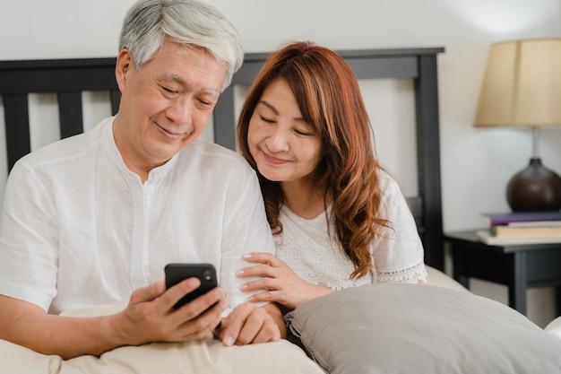 Aziatisch hoger paar die mobiele telefoon thuis met behulp van. aziatische hogere chinese grootouders, echtgenoot en vrouw gelukkig na kielzog omhoog, lettend op film liggend op bed in slaapkamer thuis in het ochtendconcept. Gratis Foto