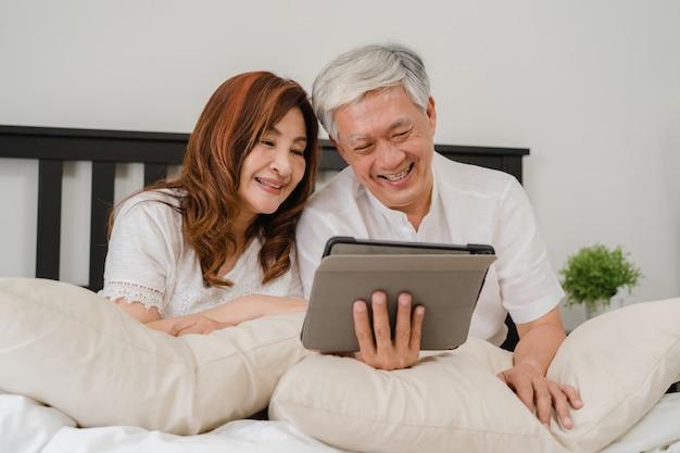 Aziatisch hoger paar die tablet thuis gebruiken. aziatische hogere chinese grootouders, echtgenoot en vrouw gelukkig na kielzog omhoog, lettend op film liggend op bed in slaapkamer thuis in het ochtendconcept. Gratis Foto