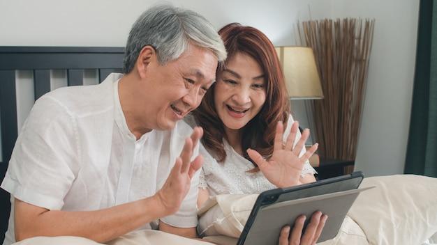 Aziatisch hoger paar die tablet thuis gebruiken. aziatische hogere chinese grootouders, videovraag die met de jonge geitjes van het familiekleinkind spreken terwijl thuis het liggen op bed in slaapkamer in het ochtendconcept. Gratis Foto