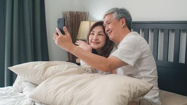 Aziatisch hoger paar selfie thuis. aziatische hogere chinese grootouders, echtgenoot en vrouw het gelukkige gebruiken mobiele telefoon selfie na kielzog omhoog liggend op bed in slaapkamer thuis in het ochtendconcept. Gratis Foto
