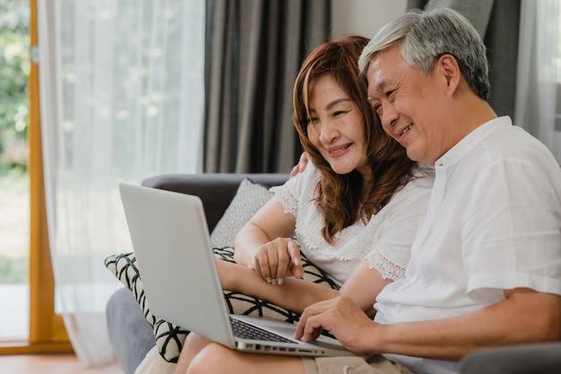 Aziatisch hoger paarvideogesprek thuis. aziatische hogere chinese grootouders, die laptop videovraag gebruiken die met de jonge geitjes van het familiekleinkind spreken terwijl thuis het liggen op bank in woonkamerconcept. Gratis Foto