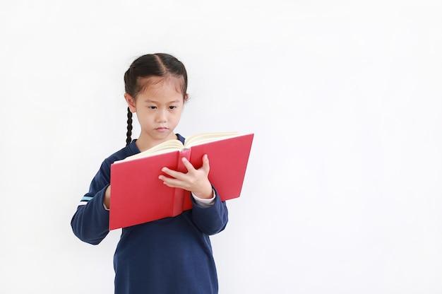 Aziatisch jong geitjemeisje die in toevallige schooluniform open boek houden dat over witte achtergrond in studioschot wordt geïsoleerd. Premium Foto