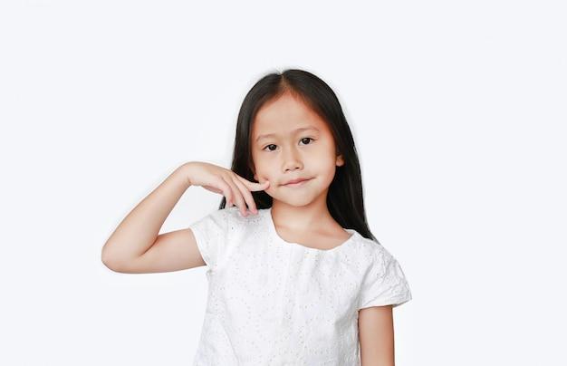 Aziatisch jong geitjemeisje die vinger op wang houden Premium Foto