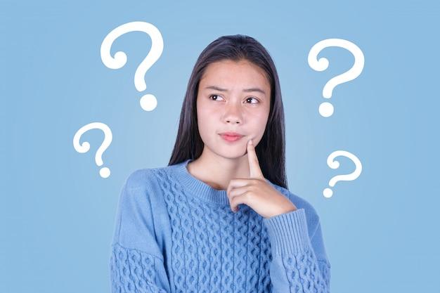 Aziatisch jong meisje met vraagtekens op blauwe achtergrond Premium Foto