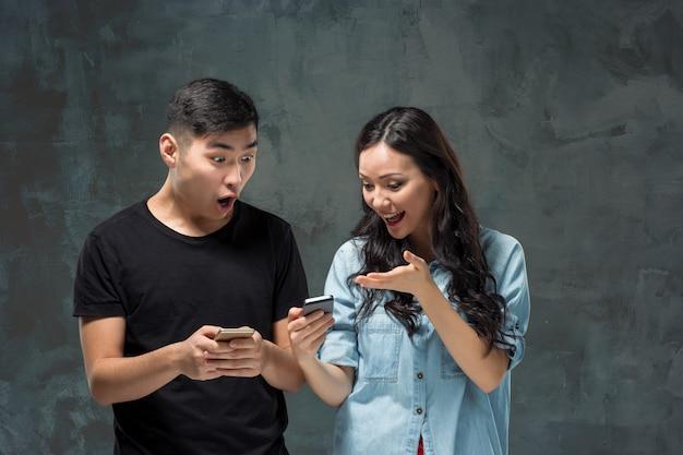Aziatisch jong paar die cellphone, close-upportret gebruiken. Gratis Foto