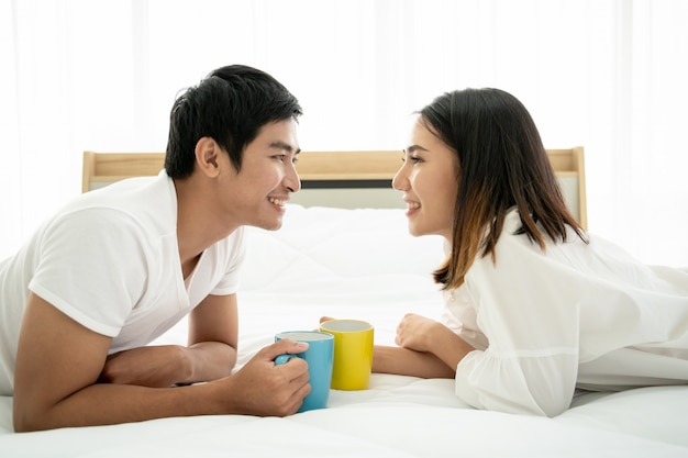 Aziatisch jong paar die samen met koffie in de ochtend in slaapkamer genieten van Premium Foto