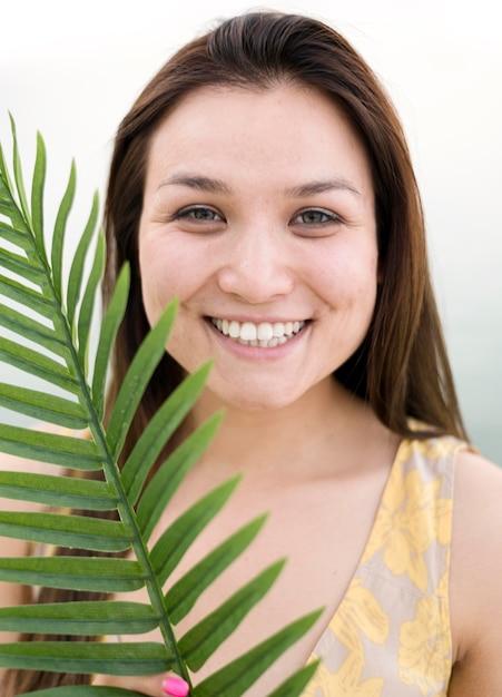 Aziatisch jong vrouwelijk model en tropisch blad Gratis Foto