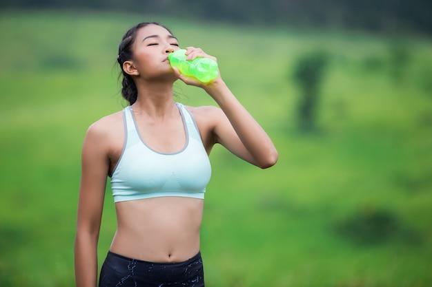 Aziatisch jong vrouwen drinkwater na het aanstoten van zonreeks Premium Foto