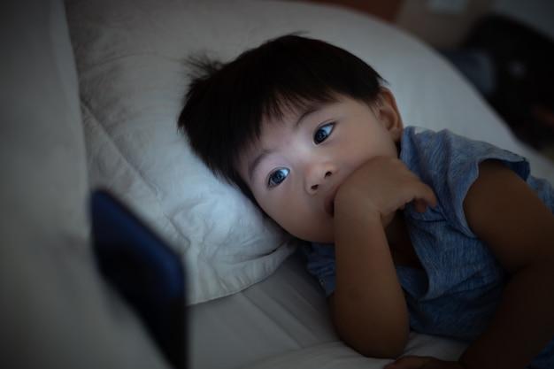 Aziatisch kind dat op bed ligt en op mobiele telefoon speelt Premium Foto