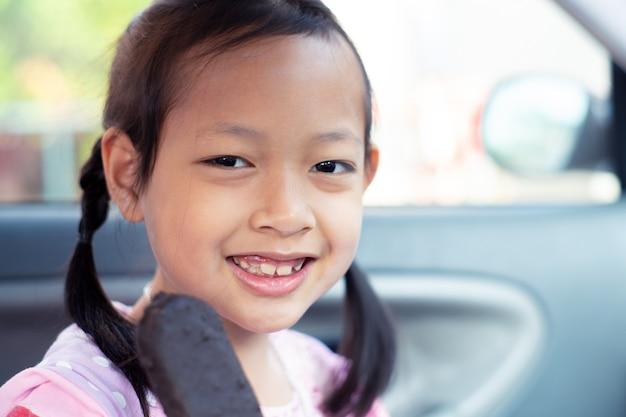 Aziatisch kindmeisje die gelukkig met het eten van de staaf van het chocoladeroomijs in auto voelen Premium Foto