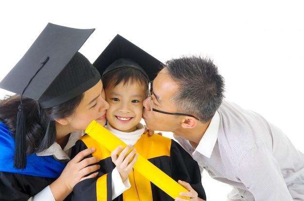 Aziatisch kleuterschoolkind in graduatietoga en barst die door haar ouder tijdens graduatie wordt gekust Premium Foto