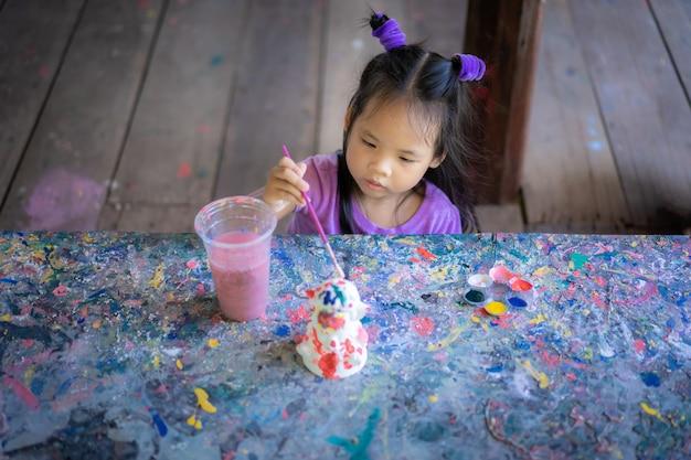 Aziatisch leuk meisje dat pret heeft om op stucopop te schilderen Premium Foto