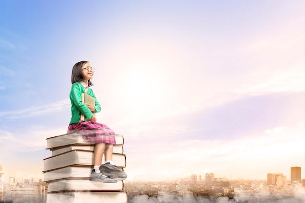 Aziatisch leuk meisje die met glazen het boek houden terwijl het zitten op de stapel van boeken met stad en blauwe hemel Premium Foto