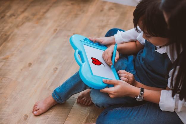 Aziatisch mamma die leuke jongen onderwijzen aan het trekken van rood hart in raad met kleurenpen Premium Foto