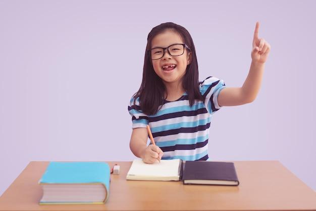 Aziatisch meisje dat een boek op lijst schrijft. wijsvinger tonen met open mond, geïsoleerd op een grijze achtergrond Premium Foto