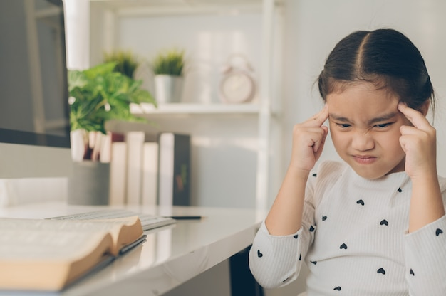 Aziatisch meisje dat hoofdpijn krijgt van huiswerk Premium Foto