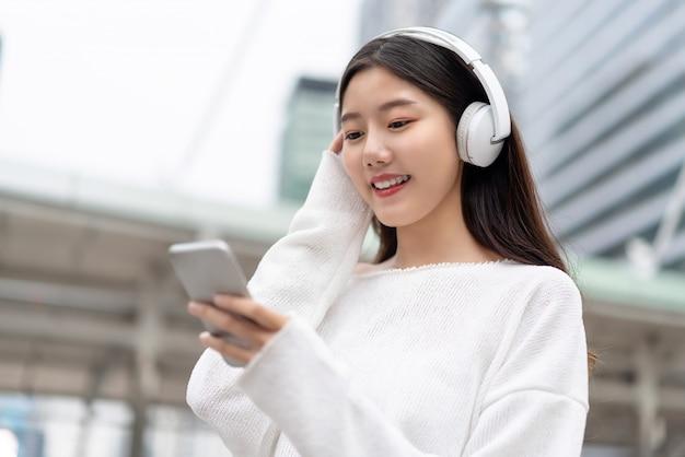 Aziatisch meisje dat hoofdtelefoons draagt die aan streaming muziek van slimme telefoon luisteren Premium Foto