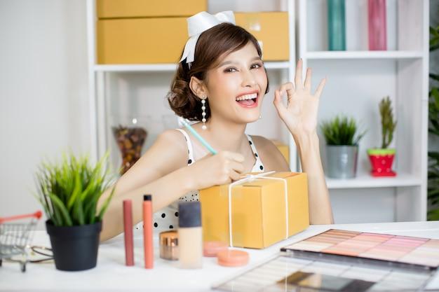 Aziatisch meisje dat thuis bureau en sorterende pakketpostdoos aan leveringsdienst aan klant werkt Gratis Foto