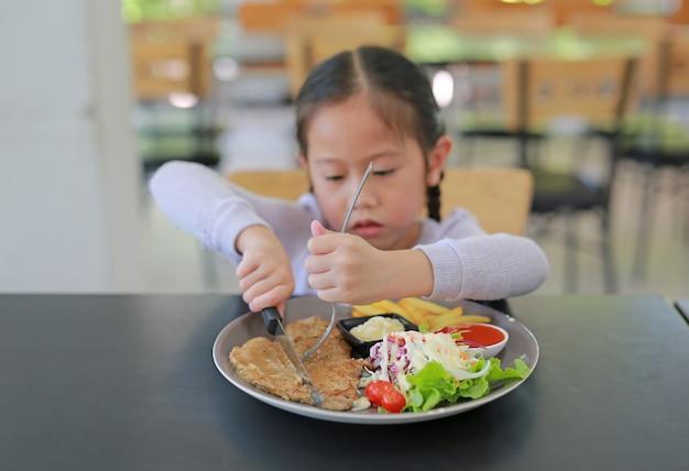 Aziatisch meisje dat varkensvleeslapje vlees en plantaardige salade op de lijst eet. Premium Foto