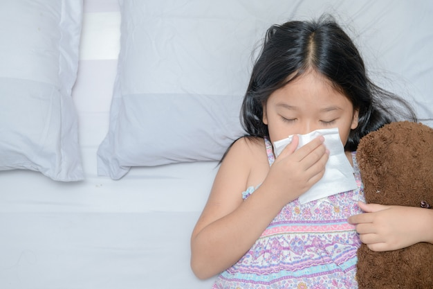 Aziatisch meisje die de neus blazen door weefsel Premium Foto