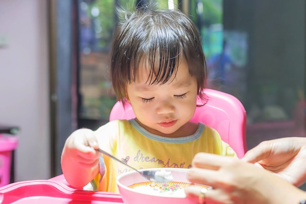 Aziatisch meisje die gebraden worsten in de aluminiumkom thuis eten dichtbij venster Premium Foto