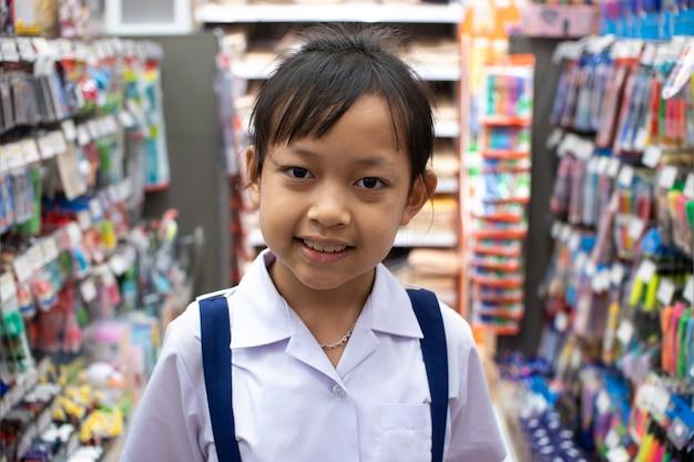 Aziatisch meisje in kantoorbehoeftenopslag het kopen pennen en schoollevering Premium Foto