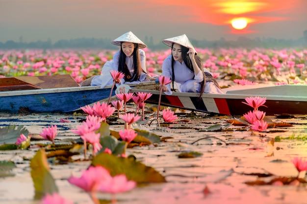 Aziatisch meisje in nationaal kostuum van de zitting van vietnam op de boot in rode lotusbloemoverzees in undon thani, thailand. Premium Foto