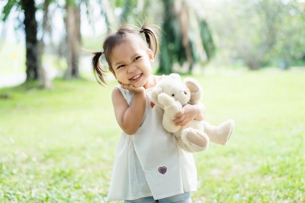 Aziatisch meisje rust in het voorjaar park. klein kind plezier in het park. Premium Foto