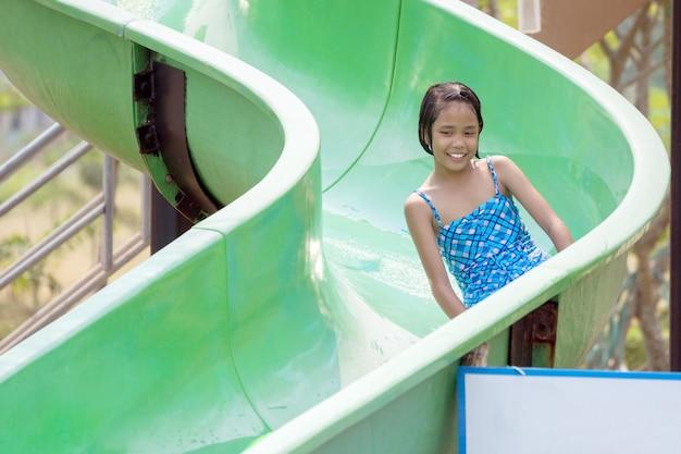 Aziatisch meisje veel plezier met het spelen van een dia in het waterpark. Premium Foto