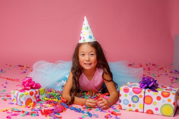 Aziatisch meisje viert verjaardag, confetti op roze Premium Foto