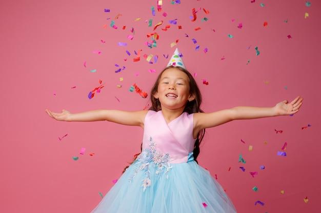 Aziatisch meisje viert verjaardag klappen vangt confetti op roze Premium Foto