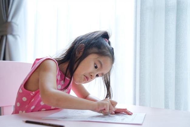 Aziatisch meisjes leuk jong geitje gebruikend gom op papier om te wissen wat zij had geschreven. Premium Foto