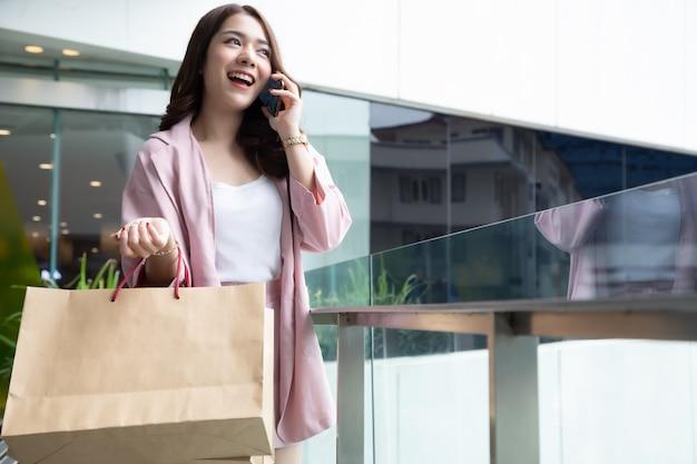 Aziatisch mooi meisje dat op de telefoon met vriend spreekt en het winkelen zak houdt Premium Foto