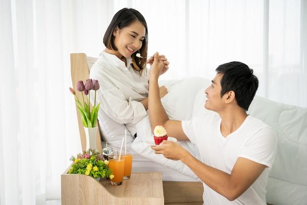 Aziatisch paar dat een cake en een jus d'orange in slaapkamer eet, concept leuk paar. Premium Foto