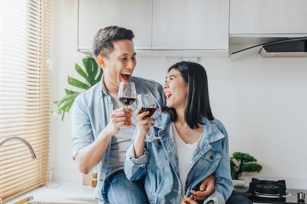 Aziatisch paar dat in liefde en rode wijn in de keuken lacht drinkt Premium Foto
