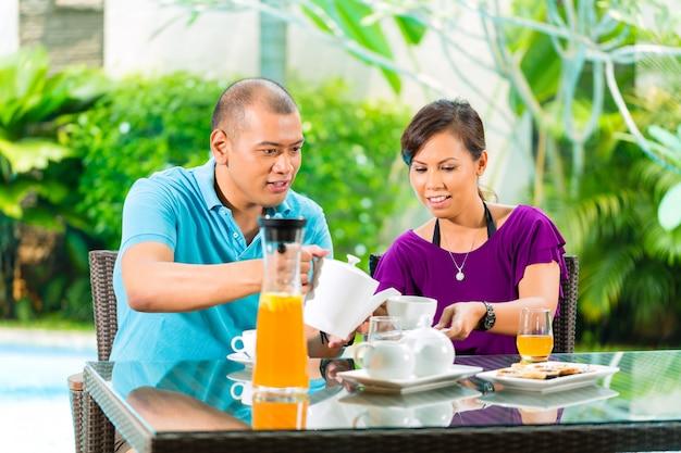 Aziatisch paar dat koffie op huisportiek heeft Premium Foto