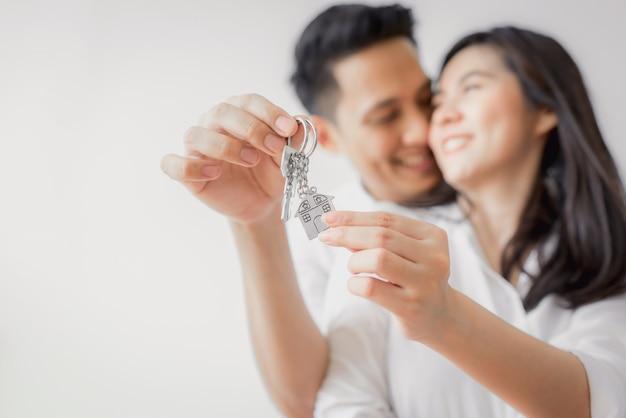 Aziatisch paar dat sleutel toont tot nieuw huis Premium Foto