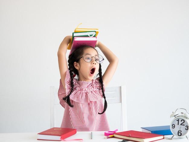 Aziatisch schattig meisje met boek op het bureau Premium Foto
