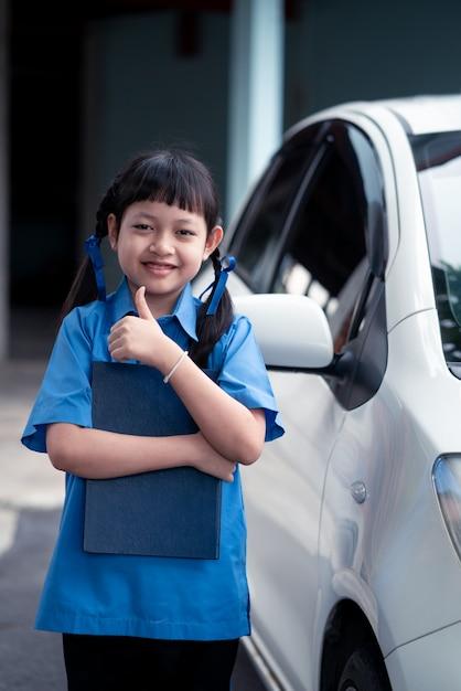 Aziatisch schoolmeisje met een boek met staande kant van de auto. terug naar school-concept Premium Foto